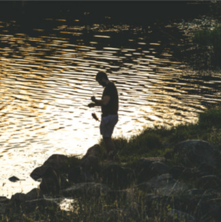 Man fishing beside stream